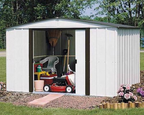 Arrow Newburgh 8x6 Steel Shed Kit (NW86) Assembled in the backyard with lawn and garden tools inside.